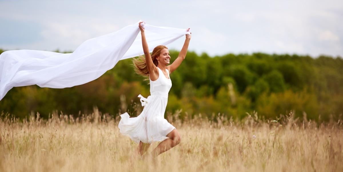Junge Frau rennt über eine Wiese